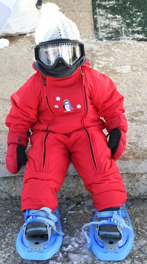 A child in red snowsuit is ready for winter fun.