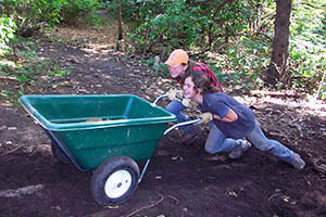 Two adolescent students on a Montessori camping and work trip push a wheelbarrow together.