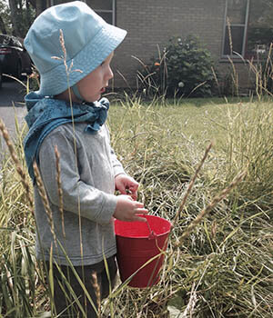 A child holds a red bucket, illustrating principles from Montessori from the Start.