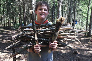 An adolescent boy on a Montessori Secondary Level camping and work trip gathers wood.