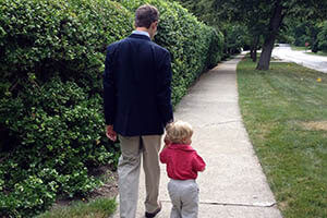 A father and child walk hand-in-hand down a sidewalk.