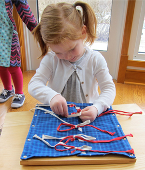 A Montessori Primary student enjoys her work on the Bow Frame at Forest Bluff School.