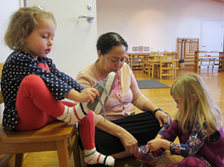 Montessori Primary students practice tying their shoes with help from the Classroom Assistant at Forest Bluff School.