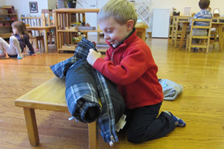 A Montessori Primary student at Forest Bluff School joyfully zips his coat onto a hanger at the beginning of the morning work cycle.
