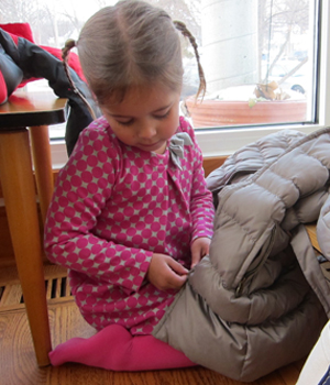 A Montessori Primary student at Forest Bluff School acquires confidence by learning to zip her coat.