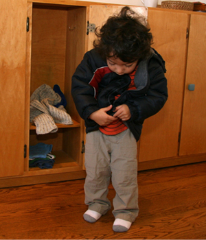 A Montessori student in the Young Children's Community at Forest Bluff School confidently prepares himself for cold weather.