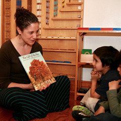 A Montessori Primary teacher reads aloud from a picture book about a tree.