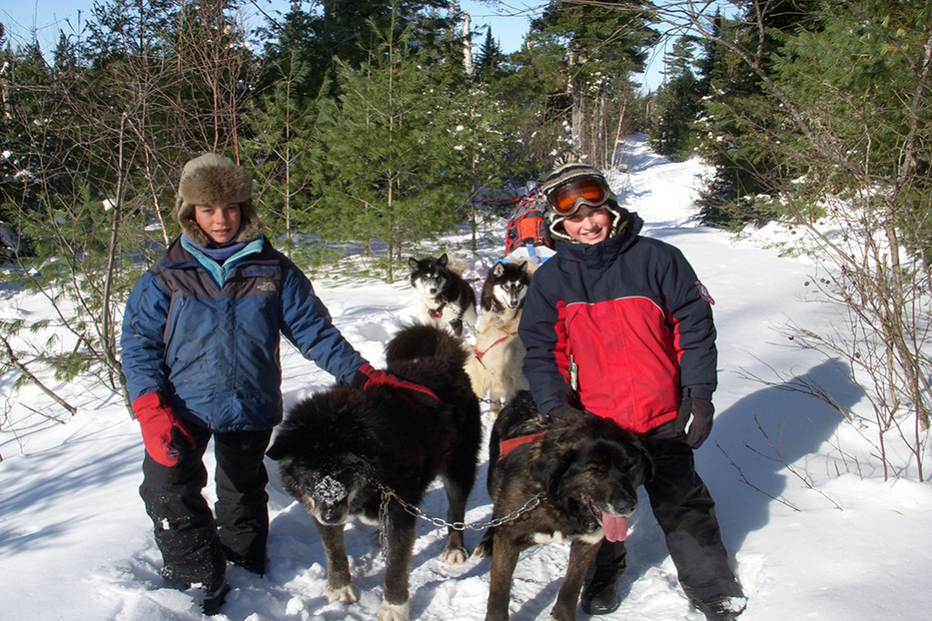 Adolescent Montessori students on a winter camping trip with sled dogs.