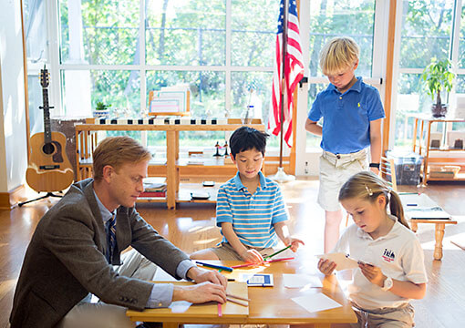 A teacher works with three Montessori elementary level students, ages six to nine
