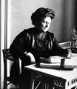 Dr. Maria Montessori writes at her desk, developing the ideas that would lead to Accredited Montessori Schools
