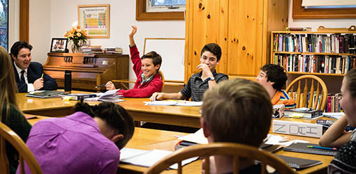 A student raises his hand in a Montessori secondary level class in session
