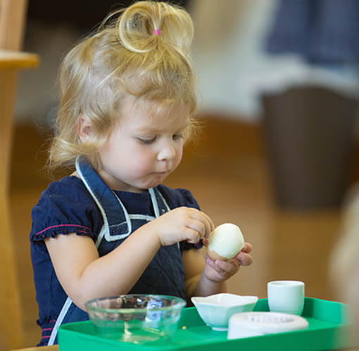 A student of the Young Children's Community peels an egg to eat