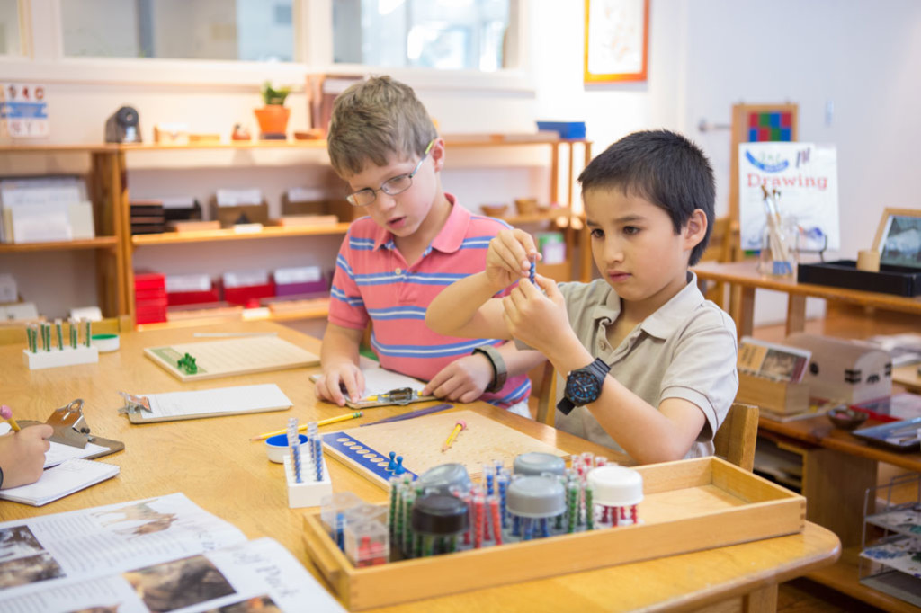 Montessori students use math materials to practice new concepts.