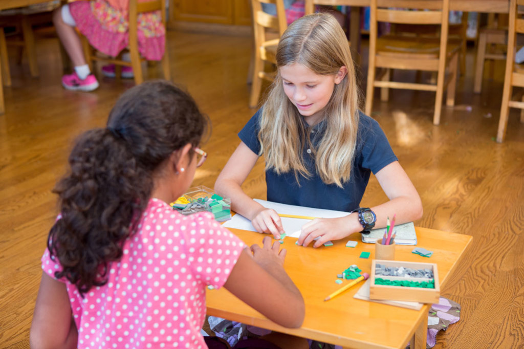 Montessori students work together at a wooden table.
