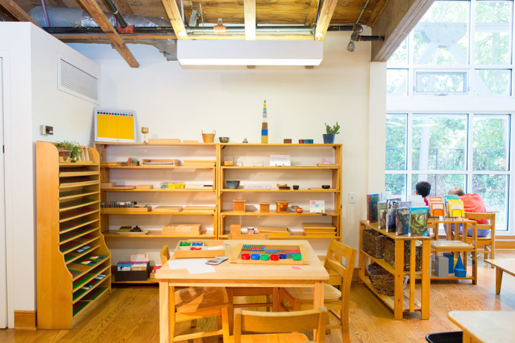 A Montessori classroom with wooden shelves and tables.