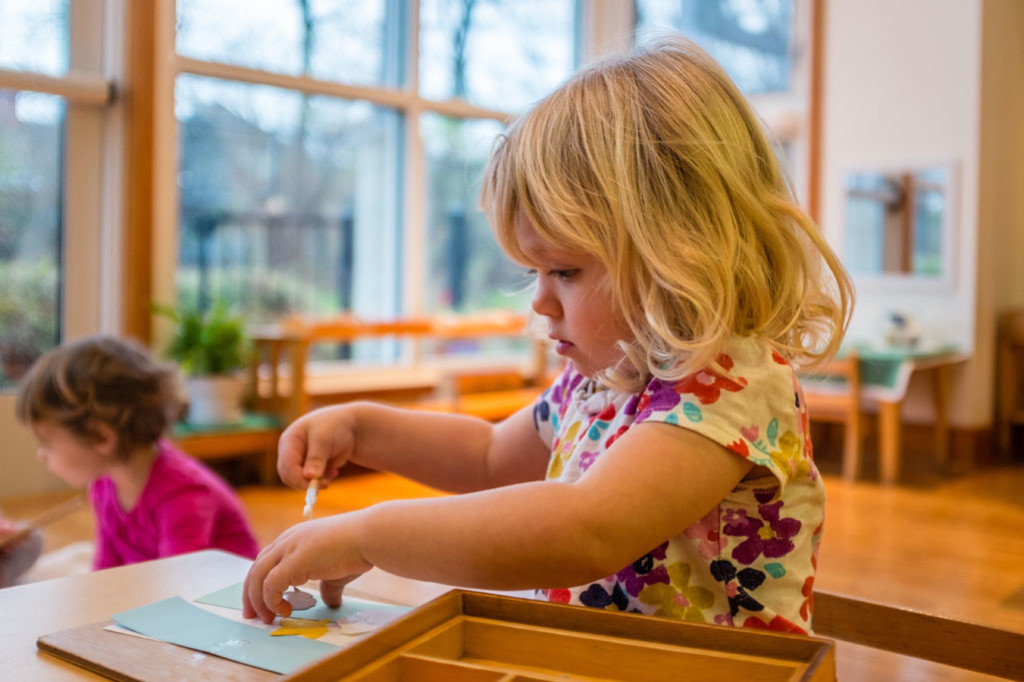 A girl in a Montessori Young Children's Community pastes shapes on a paper independently.