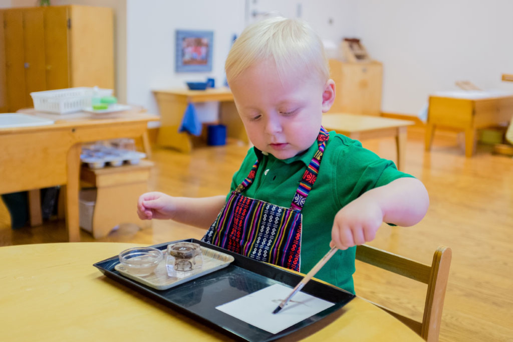 A boy in a Montessori Young Children's Community paints independently.