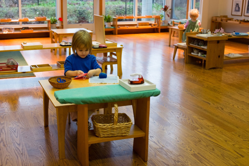 A young girl in a Montessori Young Children's Community sews independently.