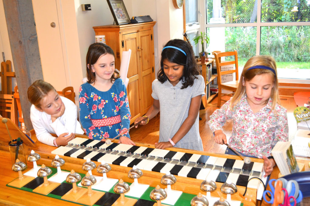 Students in a Montessori classroom make music together with bells and bars.