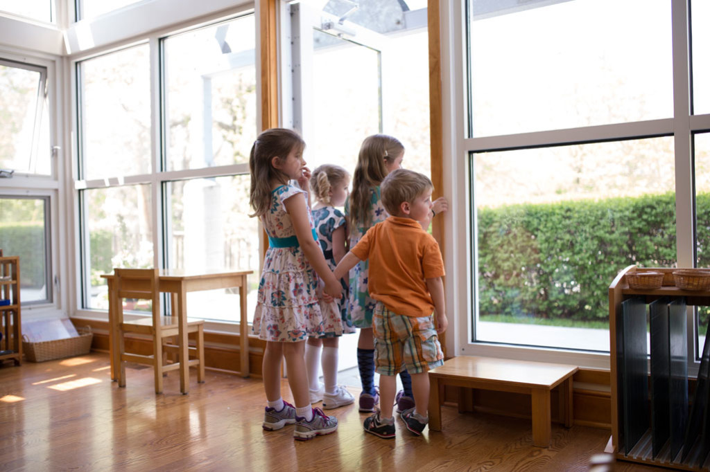 Children in a Montessori Primary classroom hold hands while waiting patiently in line for a walk outside.