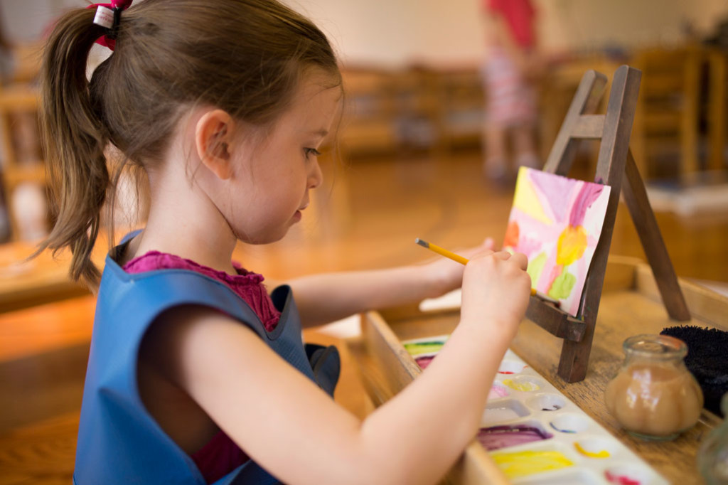 A Montessori student in a Primary classroom paints with watercolors.