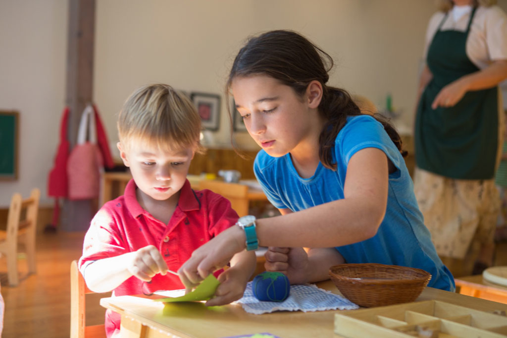 An older Montessori student assists a younger student with sewing.