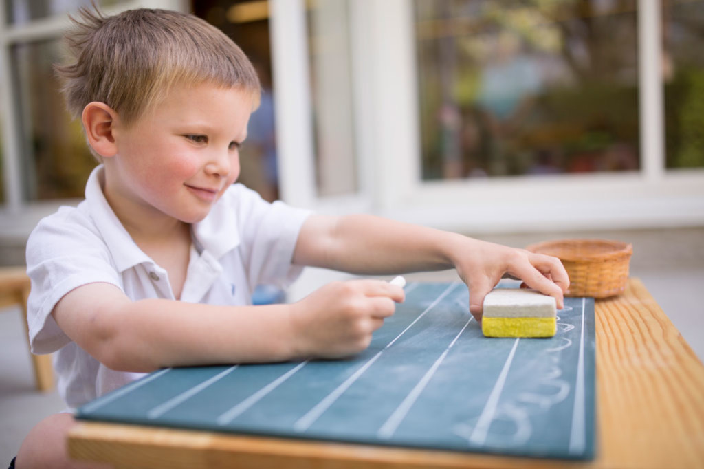 A Montessori student practices his cursive handwriting with chalk and a small chalkboard.