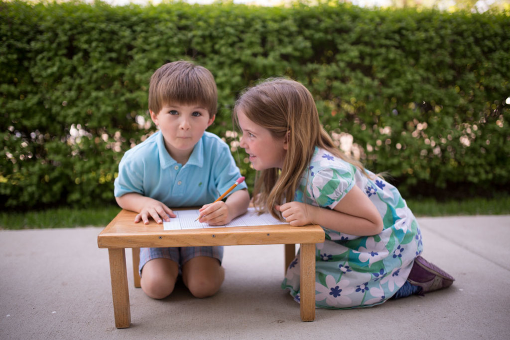 Montessori children work together at a low table on an outdoor patio.