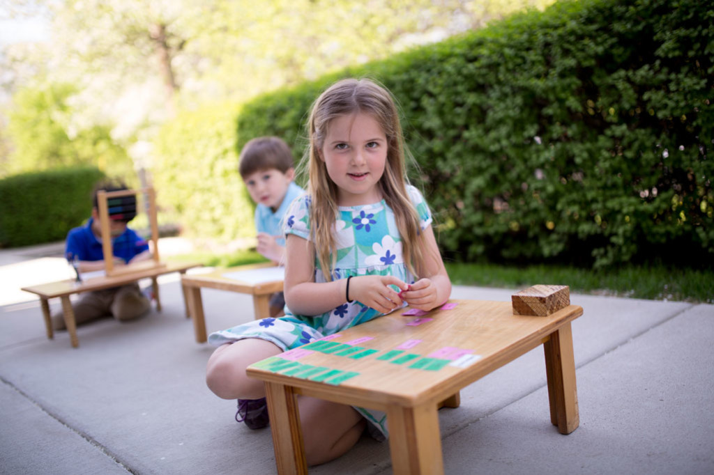 A Montessori student works at a low, wooden table outside of her Primary classroom.