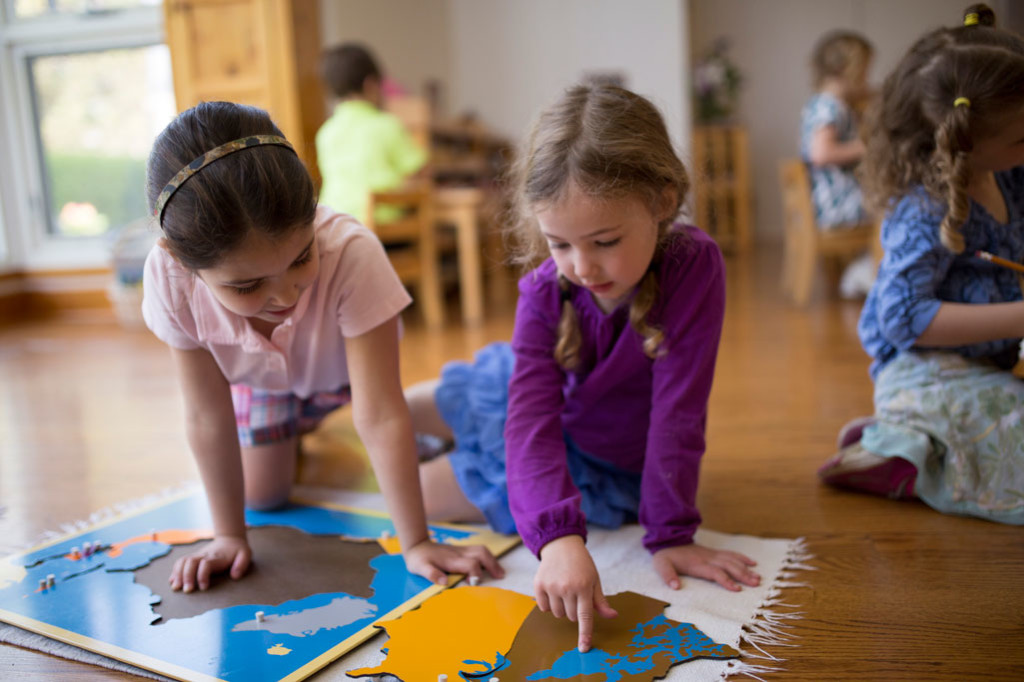 Girls in a Montessori Primary classroom work together on a puzzle map.