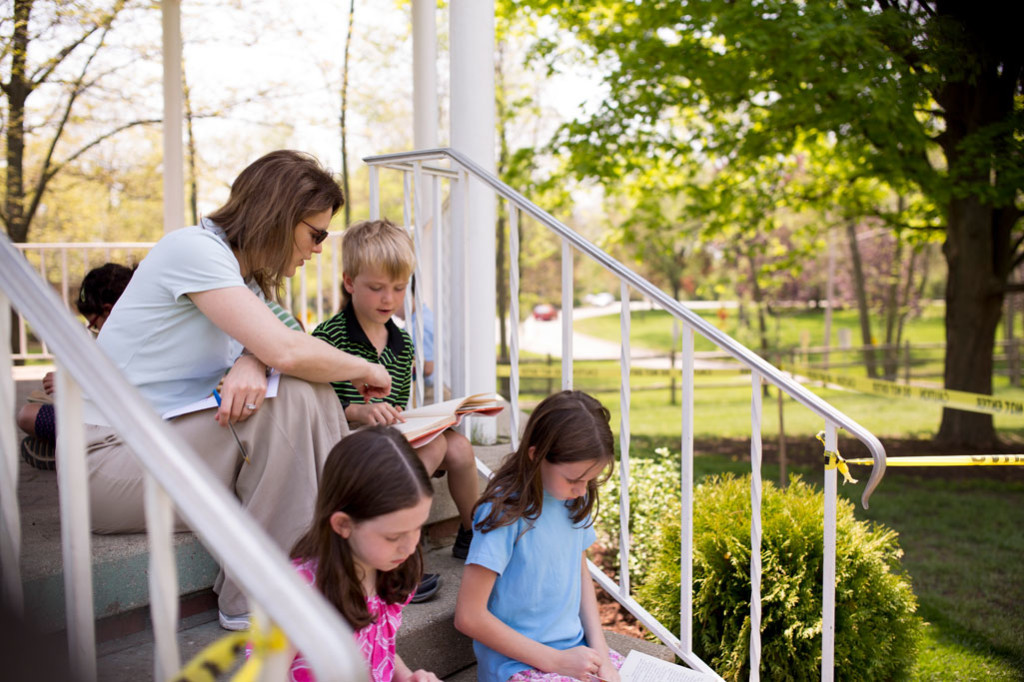 Montessori students read outside on the steps of a gazebo near Forest Bluff School.