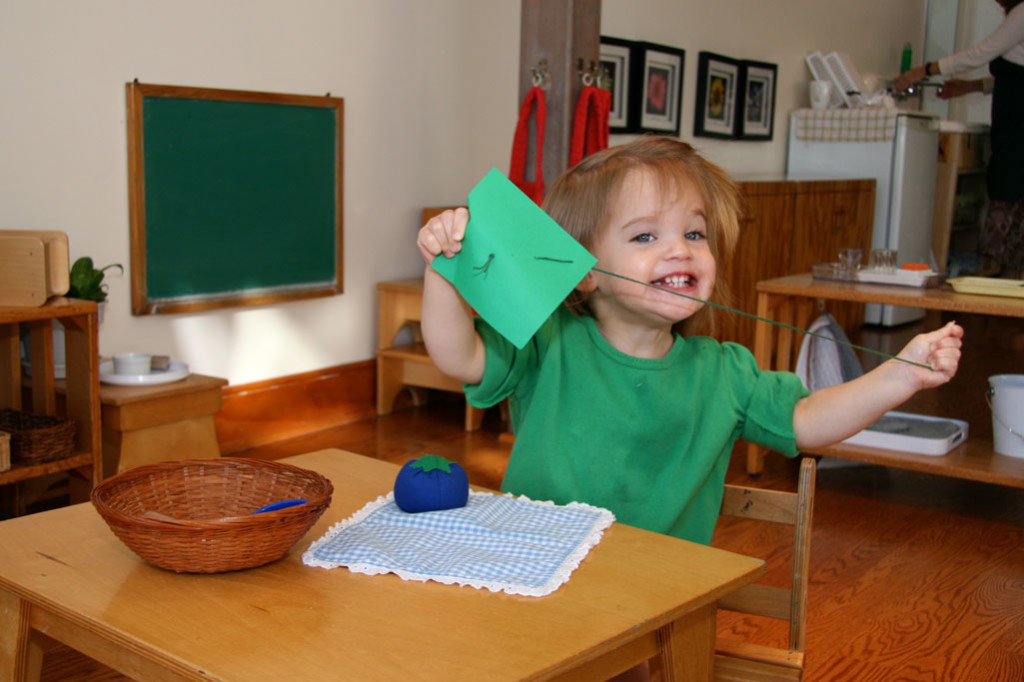 A child in a Montessori Young Children's Community joyfully sews a piece of paper.