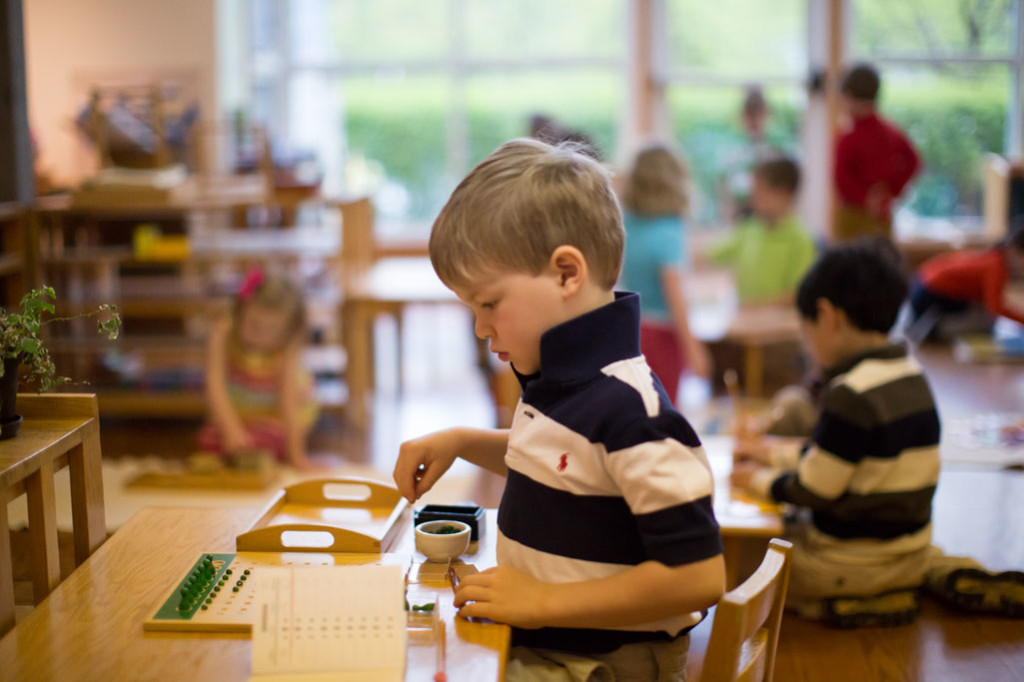 A student in a Montessori classroom uses small wooden beads for his math work.
