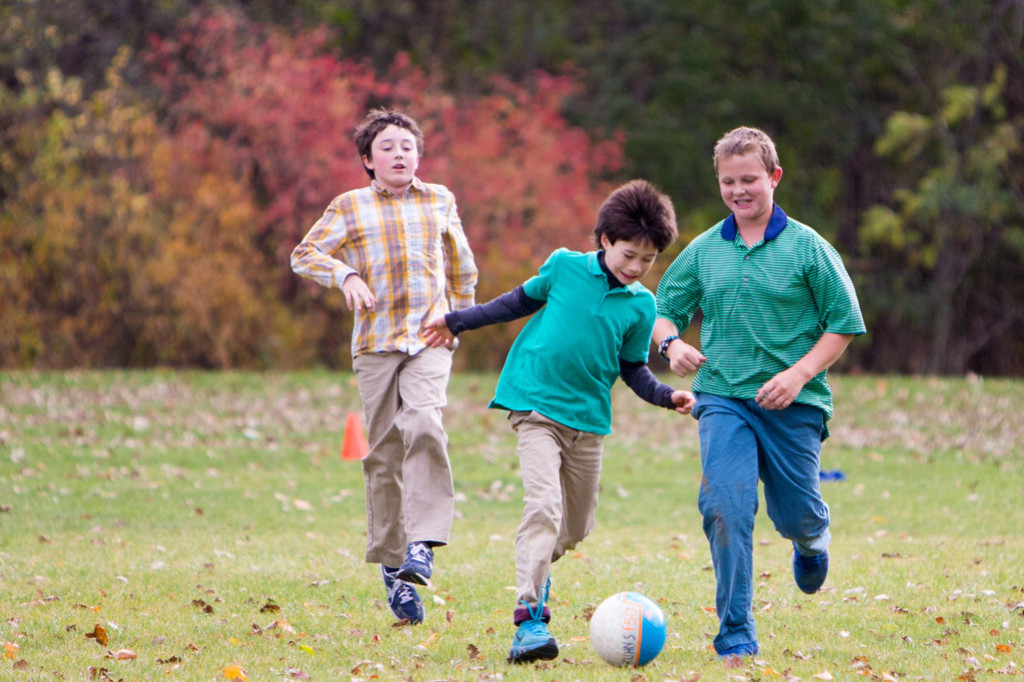 Forest Bluff School students play soccer in an open field.