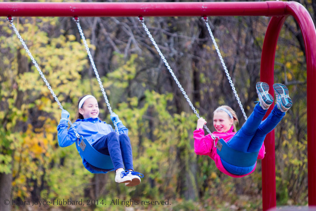 Girls enjoy the outdoors while swinging at a playground.
