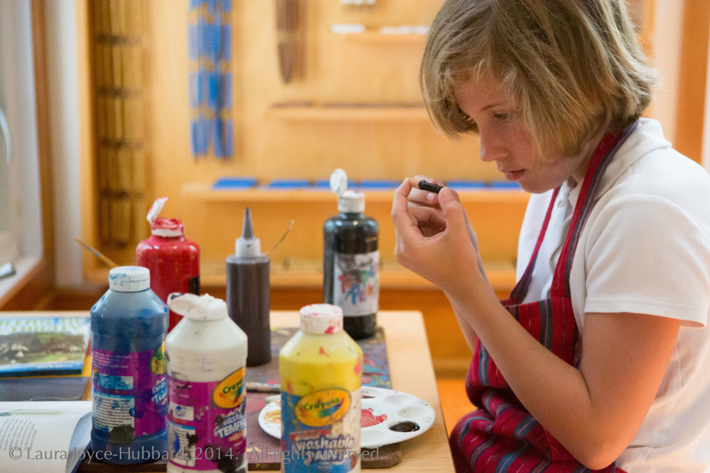 A girl in a Montessori classroom paints artwork for a project.
