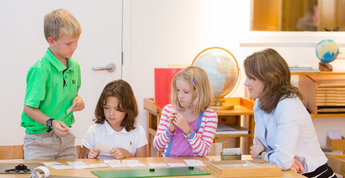 Three children discover why Montessori is a unique educational experience while learning collaboratively with their teacher in a classroom