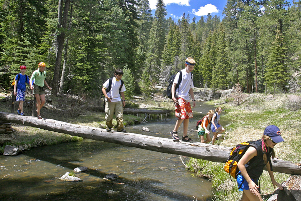 Montessori students on a camping trip walk across a log to cross a stream.