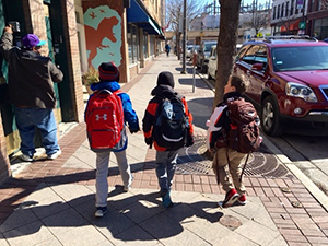 Three elementary students walk down the street in Evanston during an educational excursion