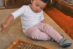 A toddler plays with a wooden xylophone.