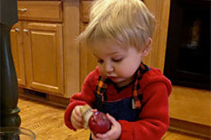 A young child peels a potato by himself.