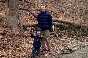 Father and son enjoy the outdoors together in a wooded area in autumn.