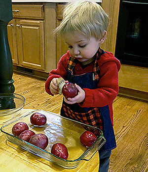 A boy scrubs potatoes in an example of independence in the first plane of development