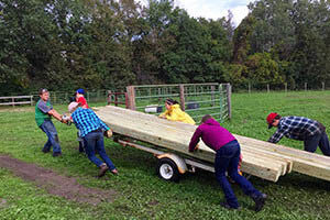 Students on a Montessori camping and work trip work together to haul large pieces of lumber for a construction project.