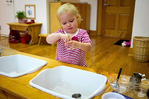 A child in the Young Children's Community uses a sink in an activity appropriate in the stages of development