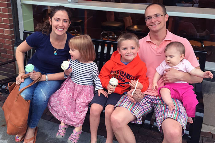 A family sits together outside on a bench, exemplifying the journey of a Montessori parent