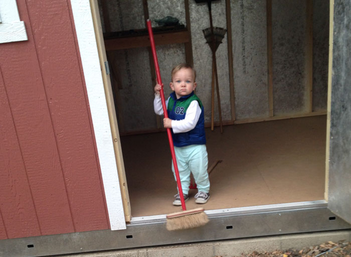 A toddler holds a broom in a shed, ready to help with the household work.