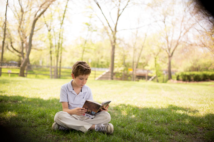 A Montessori student reads a book in a field.