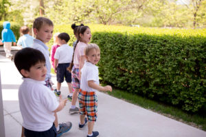 Teaching good manners in public demonstrated by children standing attentive in line.