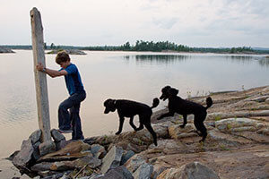 A boy uses self-directed playtime to explore around a lake with two dogs